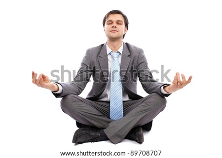 Young businessman meditating, sitting on the floor isolated on white background - stock photo