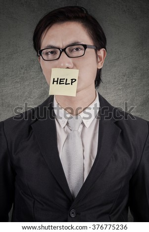 Young businessman needs help, showing a paper note attached on his mouth with a help text