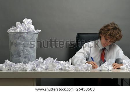 Young businessman next to stack of crumpled paper - stock photo