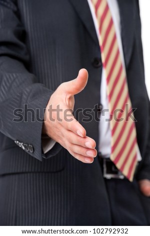 Young businessman offering a handshake, close-up photo - stock photo