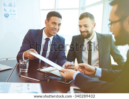 Young businessman offering his partner to sign contract after negotiation - stock photo
