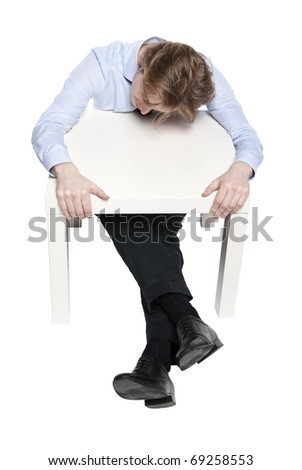Young businessman, office worker or student sleeping at funny small table. Studio photo of sleeping man. Isolated.