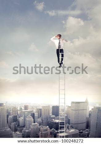 Young businessman  on a ladder over a big city looking ahead - stock photo