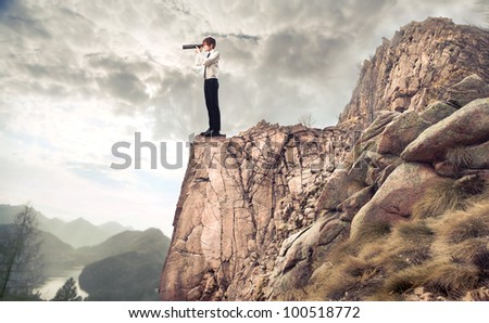 Young businessman on a mountain peak using a telescope - stock photo