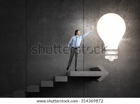 Young businessman on ladder reaching hand to touch glowing light bulb - stock photo
