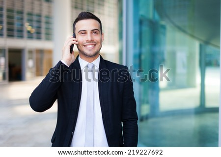 Young businessman on the phone outdoor - stock photo