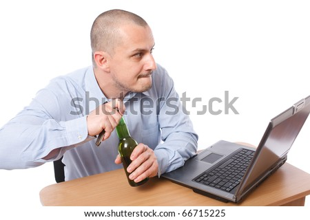 Young businessman opening a bottle of beer in the office - illegal alcohol drinking at work