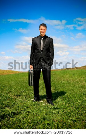 Young businessman outdoor holding a suitcase. - stock photo