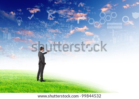 Young businessman outdoor with business symbols on the sky background