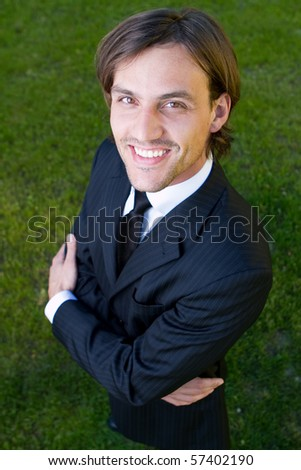 Young businessman over a green grassy background. Fresh smiling modell with longer hair. - stock photo