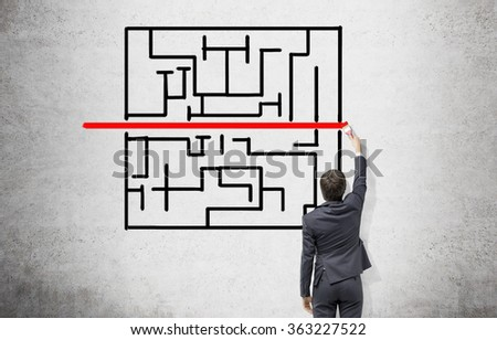 Young businessman painting a black labyrinth on the concrete wall with a horizontal red line in the middle. Back view. Concept of finding a solution.