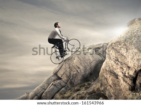 young businessman pedaling a bicycle on the rocks - stock photo