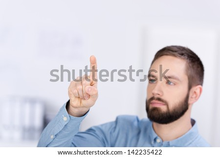 Young businessman pointing while looking away in office - stock photo
