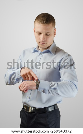 Young businessman points to his watch on his arm. Isolated on white background. - stock photo