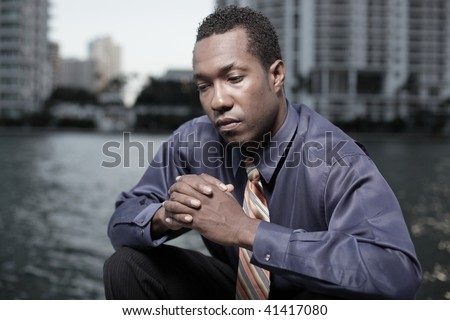 Young businessman pondering with buildings in the background - stock photo