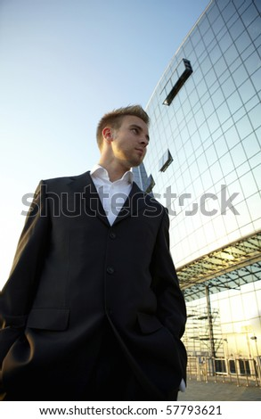 Young businessman portrait against urban background