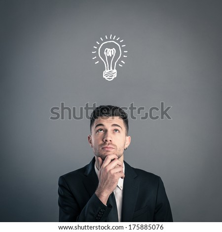 Young businessman portrait having an idea against dark background. Conceptual image.