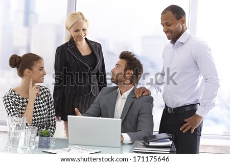 Young businessman presenting at a meeting, using laptop computer. - stock photo