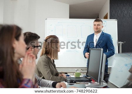 young businessman presenting new business plan to his coworkers on a meeting in a board room