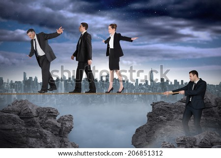 Young businessman pulling a tightrope for business people against large city on the horizon - stock photo