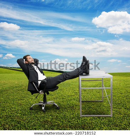 young businessman put his feet up on the table, resting and smiling. photo at outdoor - stock photo