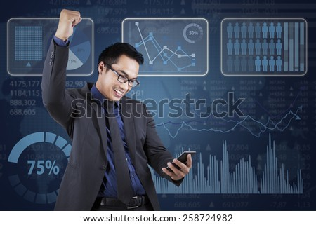 Young businessman reading good news on mobile phone and expressing success near the financial statistics - stock photo