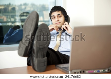 Young businessman reading his computer screen while talking on the phone, feet up on the desk.