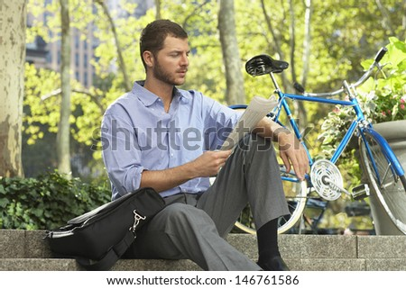 Young businessman reading newspaper by bicycle in park - stock photo