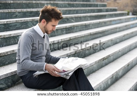 Young businessman reading newspaper in stairs. - stock photo