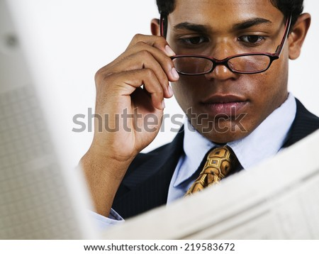 Young businessman reading newspaper over glasses - stock photo