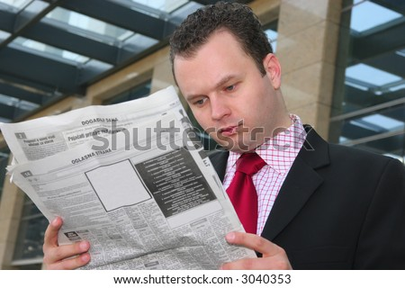 Young businessman reading newspapers with blank ads - stock photo
