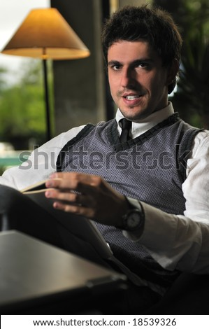 young businessman reading newspapper at luxury caffe restaurant - stock photo