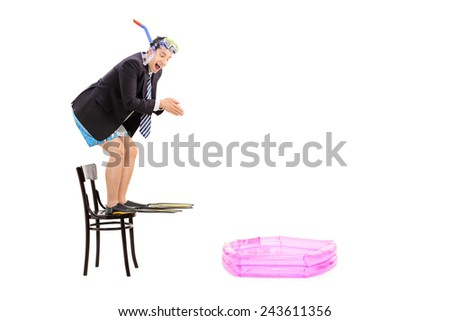 Young businessman ready to jump into a baby pool isolated on white background - stock photo