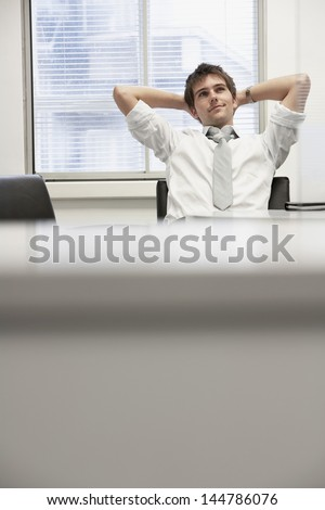 Young businessman reclining in office chair looking at ceiling - stock photo