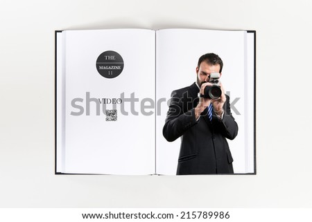 Young businessman recording video printed on book - stock photo