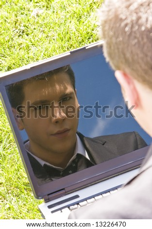 Young businessman reflected in his own computer. - stock photo