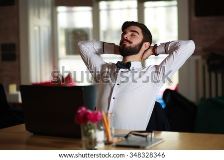 Young businessman resting at the workplace, in the office - stock photo