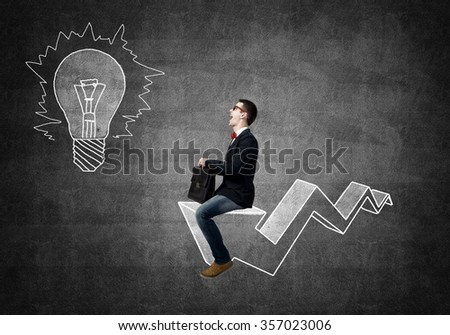 Young businessman riding drawn graph arrow going up - stock photo