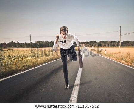 Young businessman running fast on a countryside road - stock photo