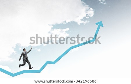 Young businessman running on increasing arrow graph