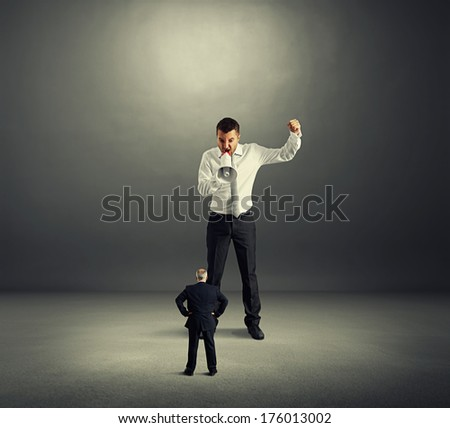 young businessman screaming at senior worker in empty dark room