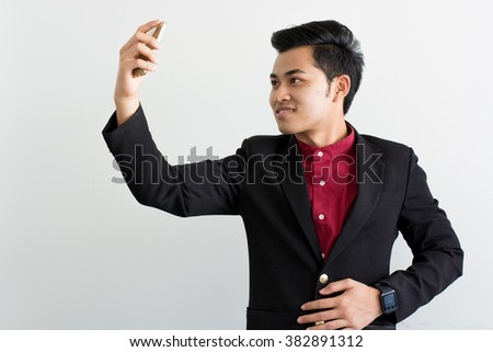 Young businessman selfie with smartphone on white background