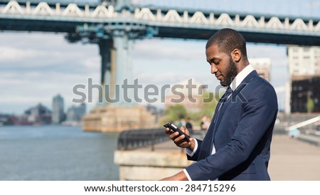 Young businessman sending text message with mobile phone phone with Manhattan Bridge in the background. Brooklyn Dumbo Park, New York City. - stock photo