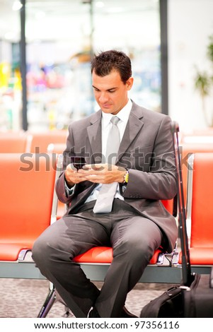 young businessman sending text messages at airport - stock photo