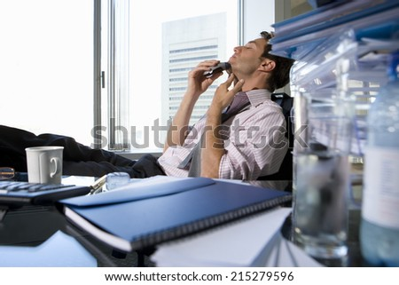 Young businessman shaving at desk in office by book, mug and glass on desk (differential focus)
