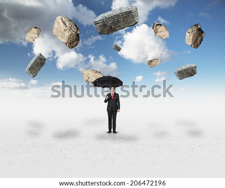 Young businessman sheltering under the black umbrella from rocks falling to the ground. - stock photo