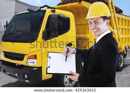 Young businessman showing clipboard with a delivery truck carrying palm fruits in the factory - stock photo