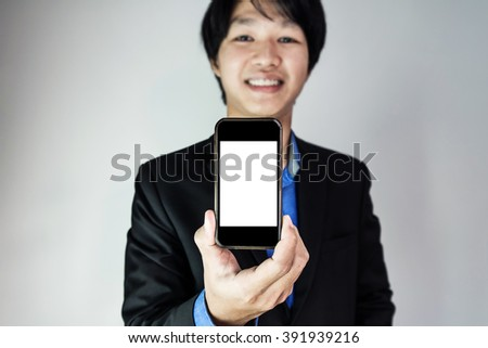 Young businessman showing smart phone, with smile face - stock photo