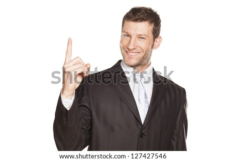 Young businessman showing something by his index finger, isolated on white. You can add extra white space with your message to the bottom. - stock photo