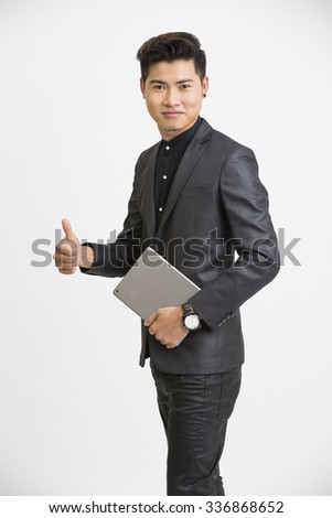 Young businessman showing thumbs up with digital tablet  - stock photo